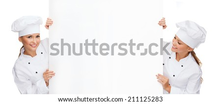 cooking, advertisement and food concept - two smiling female chefs, cooks or bakers with white blank board - stock photo