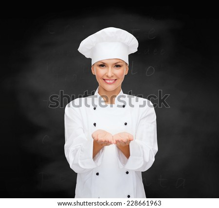 cooking, advertisement and people concept - smiling female chef, cook or baker holding something on palm of hands over blackboard background - stock photo