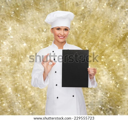 cooking, advertisement, holidays and people concept - smiling female chef, cook or baker with blank black menu paper showing ok gesture over yellow lights background - stock photo