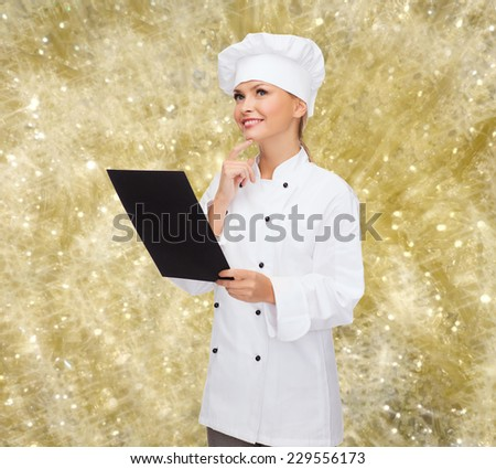 cooking, advertisement, holidays and people concept - smiling female chef, cook or baker with blank black menu paper thinking over yellow lights background - stock photo