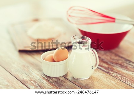 cooking and food concept - close up of jugful of milk, eggs in a bowl and flour - stock photo