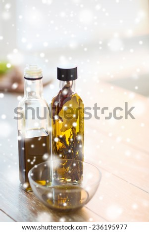 cooking and food concept - close up of two olive oil bottles and glass bowl on wooden table at home kitchen - stock photo