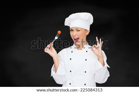 cooking and food concept - smiling female chef, cook or baker with fork and tomato showing ok sign - stock photo