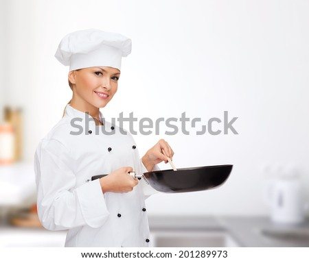 cooking and food concept - smiling female chef, cook or baker with pan and spoon - stock photo
