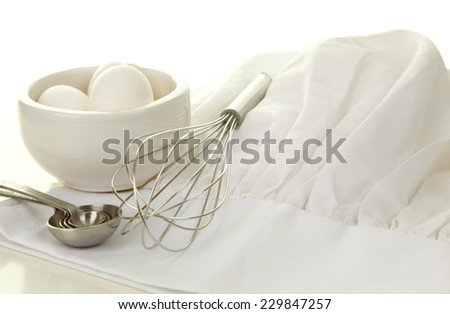 Cooking and Food Preparation Background with a Chef Hat, Eggs, a whisk and measuring spoons - stock photo