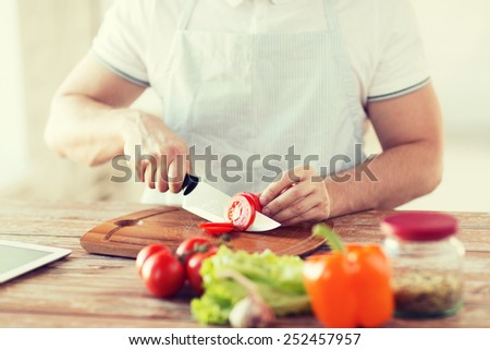 cooking and home concept - close up of male hand cutting tomato on cutting board with sharp knife - stock photo