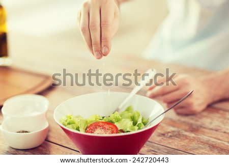 cooking and home concept - close up of male hands flavouring salad in a bowl with salt - stock photo