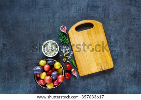 Cooking background with empty vintage cutting board, organic ingredients (potatoes, tomatoes, spices and herbs) over dark grunge table, top view. Raw vegetables from garden for healthy cooking. - stock photo