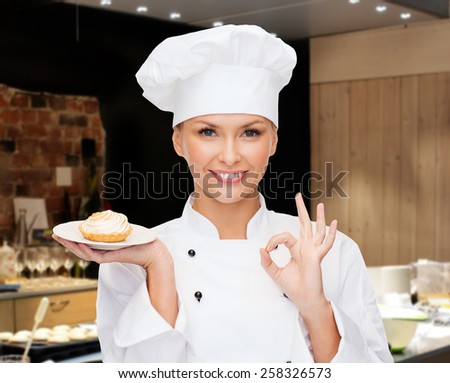cooking, bakery, people and food concept - smiling female chef, cook or baker with cupcake on plate and ok sign over restaurant kitchen background - stock photo
