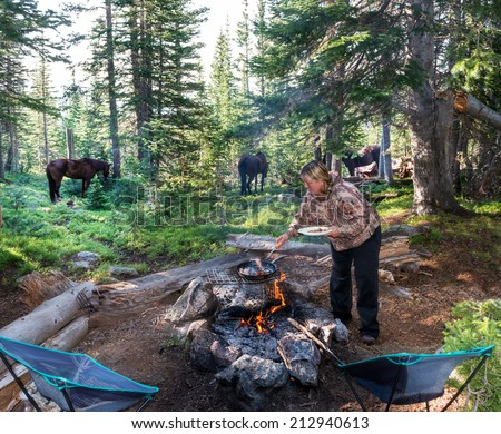 Cooking breakfast over a campfire in the Rockies with horses in the background - stock photo