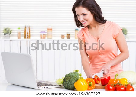 Cooking by recipe. Beautiful young woman looking at the laptop and smiling while cutting vegetables on the cutting board - stock photo