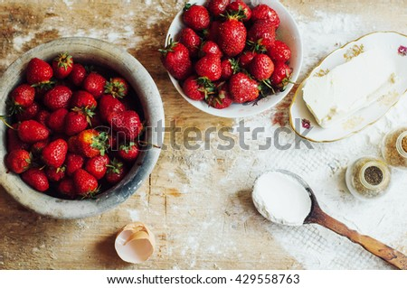 Cooking cake with fresh ingredients for preparing in cooking. Rustic dark atmosphere. Flour, eggs and fresh strawberries, cherries, butter, flour over on wooden background. Series, recipe step on step - stock photo