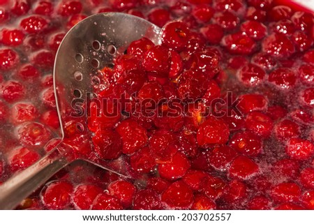 cooking cherry jam on a gas stove in the village - stock photo