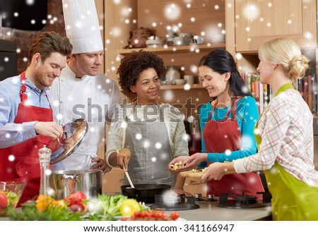 cooking class, culinary, food and people concept - happy group of friends and male chef cook cooking in kitchen over snow effect - stock photo