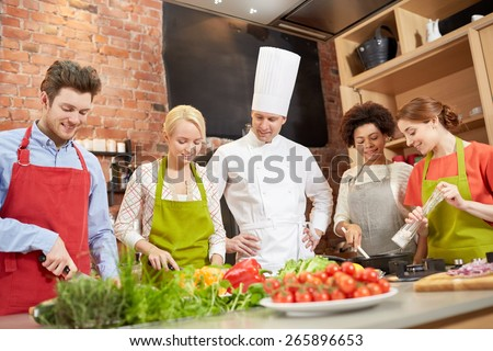 cooking class, culinary, food and people concept - happy group of friends with male chef cook cooking in kitchen - stock photo