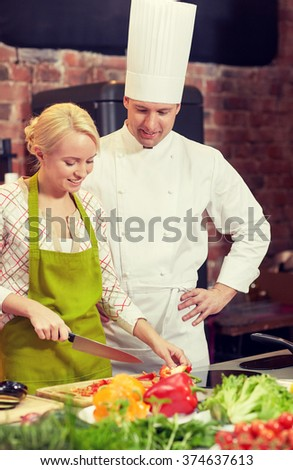cooking class, culinary, food and people concept - happy male chef cook with woman cooking in kitchen - stock photo