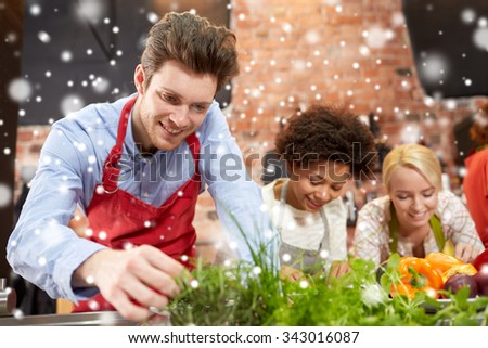 cooking class, friendship, food and people concept - happy women cooking and decorating plates with dishes in kitchen over snow effect - stock photo