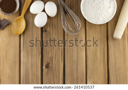Cooking concept. Top view of food ingredients and kitchen utensils for cooking on wooden background with place for your text - stock photo