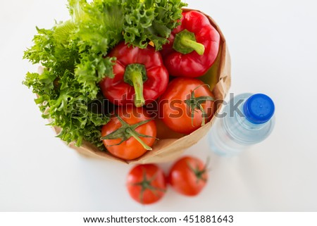 cooking, diet, vegetarian food and healthy eating concept - close up of paper bag with fresh ripe juicy vegetables and water bottle on kitchen table at home - stock photo