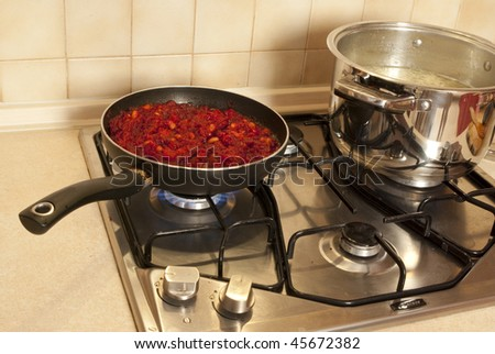 Cooking dinner. On the stove a pot of soup and pan with vegetables - stock photo