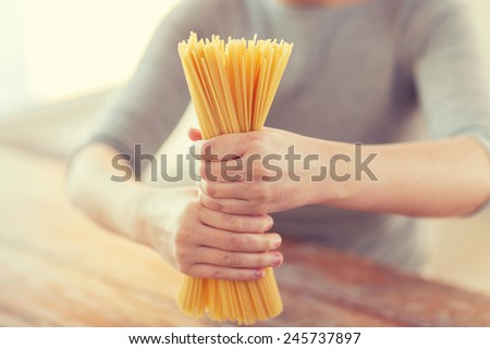 cooking, food and home concept - close up of female hands holding uncooked spaghetti pasta - stock photo