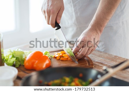 cooking, food and home concept - close up of male hand cutting pepper on cutting board at home - stock photo