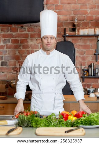 cooking, food and people concept - happy male chef cook with vegetables on restaurant kitchen table - stock photo
