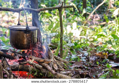 Cooking food at a campsite deep within the Amazon rainforest in Peru - stock photo
