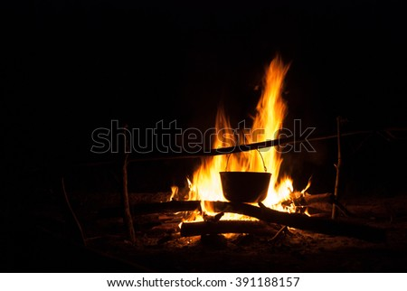 Cooking food on a fire, in the campaign. Cooking in marching pot - stock photo