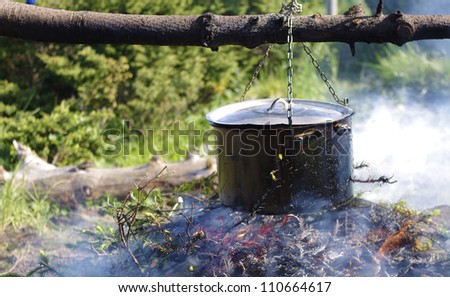 Cooking food on an open fire in the wild survival - stock photo
