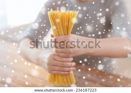 cooking, food, people and home concept - close up of female hands holding uncooked spaghetti pasta - stock photo