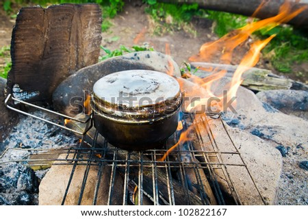 Cooking food with old tourist pot at outdoor fire place. Summer trekking activity - stock photo