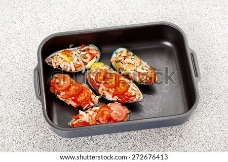 cooking fresh oysters stuffed with seafood in a baking dish  - stock photo