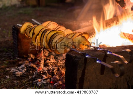 Cooking Fried potatoes  on skewers. The concept of eating outdoors in the weekend. - stock photo