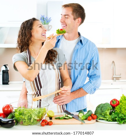 Cooking. Happy Couple Cooking Together - Man and Woman in their Kitchen at home Preparing Vegetable Salad. Diet. Dieting. Healthy Food  - stock photo