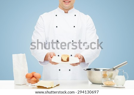 cooking, haute cuisine, food and people concept - close up of happy male chef cook with flour, eggs and butter on table baking dessert over blue background - stock photo
