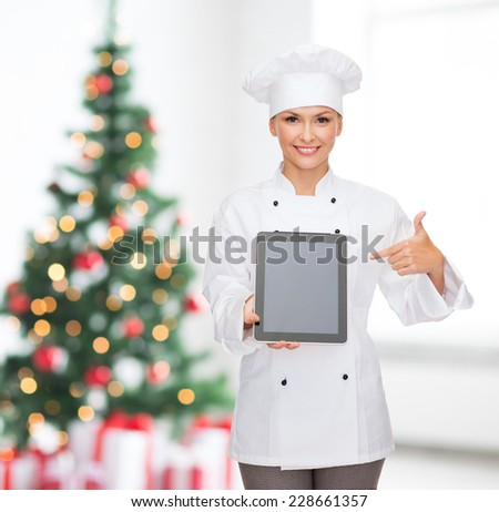 cooking, holidays, technology and food concept - smiling female chef, cook or baker with tablet pc computer pointing finger to blank screen over living room with christmas tree background - stock photo