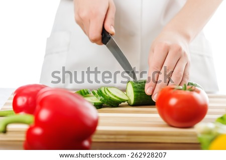 Cooking. Image of male hand with knife cutting cucumbers on wooden board  - stock photo