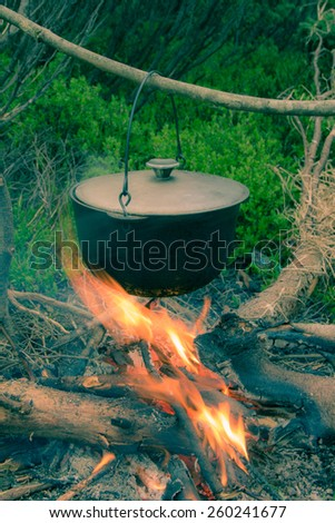 Cooking in field conditions, boiling pot at the campfire on picnic. Vintage effect with soft focus. - stock photo