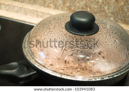 cooking in frying pan with cover on stove - stock photo