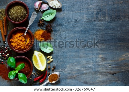 Cooking ingredients background with space for text. Spices and herbs over dark old wood. Food and cuisine concept.  - stock photo