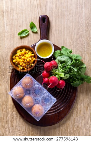 cooking Ingredients: radishes, eggs, corn. Preparation of light summer salad. Healthy food - stock photo
