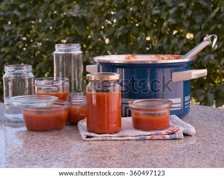 Cooking italian style homemade tomato sauce and preservation in the preservating jars in the garden. Sauce made from fresh riped tomatoes, basil leaves and onion the best for italian pasta or pizza. - stock photo