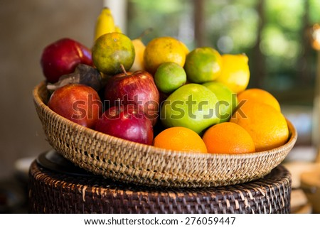 cooking, kitchen, vegetarian and food concept - basket of of fresh ripe juicy fruits at kitchen or home - stock photo