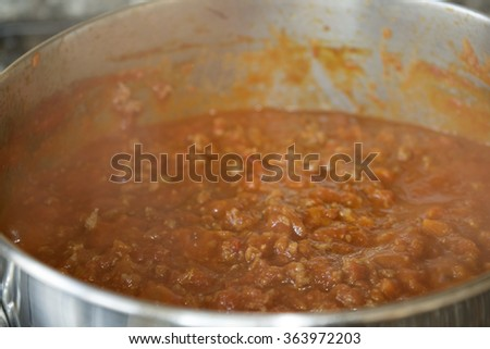 cooking of a bolognese ragu with minced beef and tomato sauce in a casserole - stock photo