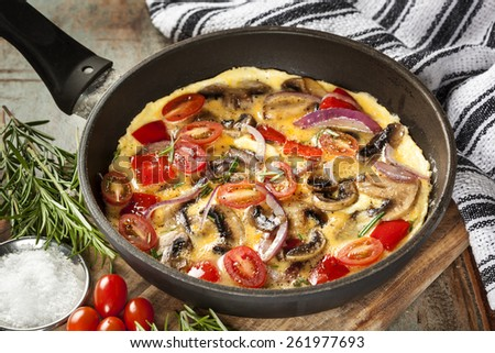 Cooking omelet in frypan, with mushrooms, cherry tomatoes, onions, capsicum and herbs. - stock photo