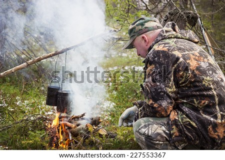 Cooking on a fire in field conditions, October, Russia - stock photo