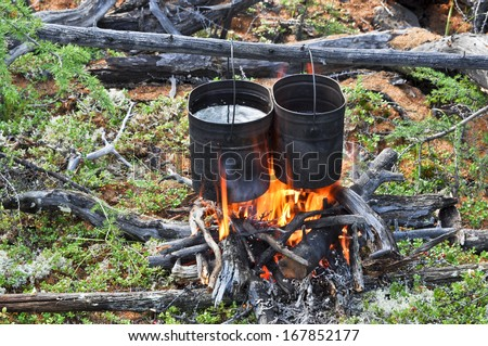 Cooking on camp fire. Russia, Eastern Yakutia, a ridge of Suntar-khayata, river Suntar. - stock photo