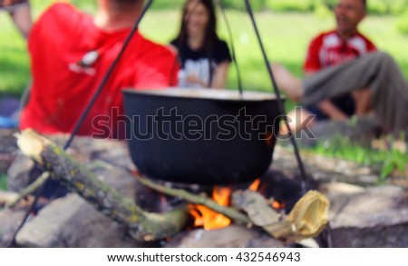 Cooking outdoors. Cauldron on a fire in the forest. Blurred - stock photo
