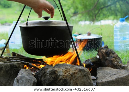 Cooking outdoors. Cauldron on a fire in the forest. On the background of the tent, a river and trees. - stock photo